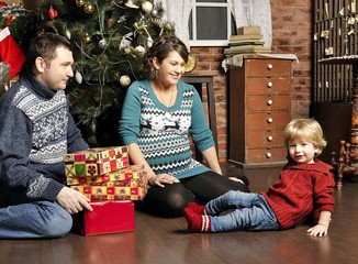 Smiling parents giving Christmas present to son at home