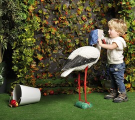 The small child plays with an artificial stork