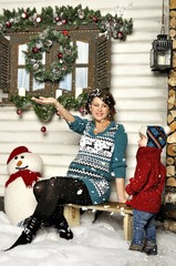 Pregnant woman sits on a bench with the child about a snowman