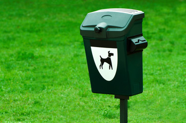 Green dog waste container in a park