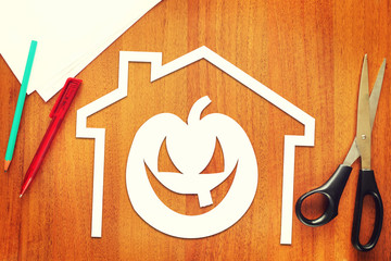 Halloween pumpkin into home cut out of paper lying on the table