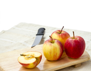 Small gala apple on wooden chopping board over white.