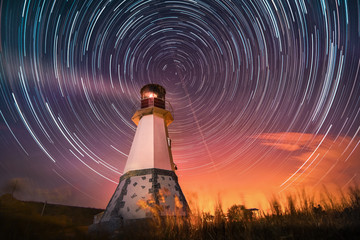 lighthouse with night sky at background stars trails