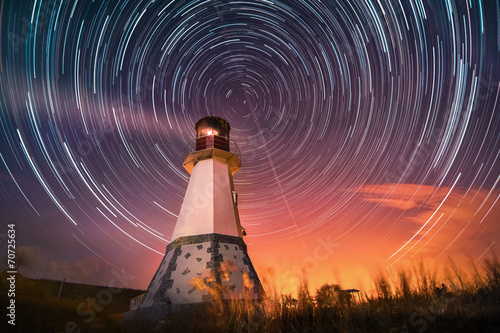 lighthouse with night sky at background stars trails - 70725634