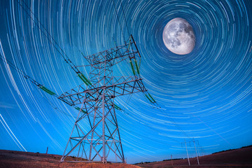 Electricity power poles on night sky and startails moon backgrou