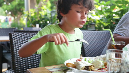 Hungry child eating at the restaurant