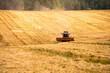 canvas print picture - Mähdrescher auf einem abgeernteten Feld