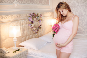 Beautiful pregnant girl in the bedroom