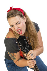 Giovane rocker tatuata che canta usando la chitarra