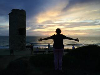 Junge Frau empfängt Sonnenuntergang mit offenen Armen