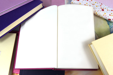 Blank pages in open book on book background
