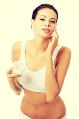 Pretty fit woman with moisturizer cream.