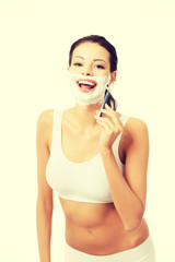 Beautiful woman shaving her face with a razor