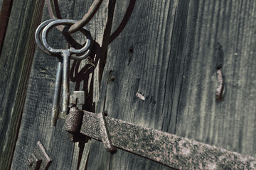 antique keys and ring agains a barn wall
