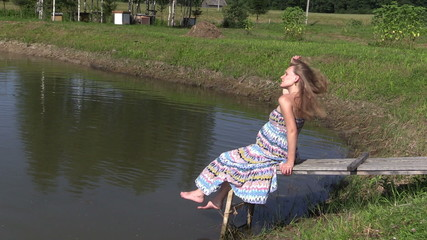Pregnant woman in long dress sit on wooden bridge near pond
