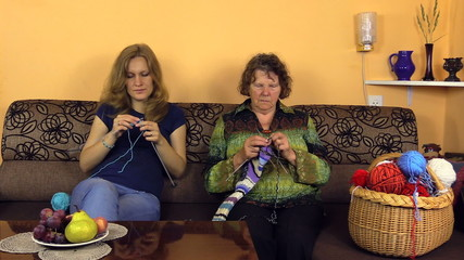 Old grandmother knit with nurse woman on sofa in nursing home
