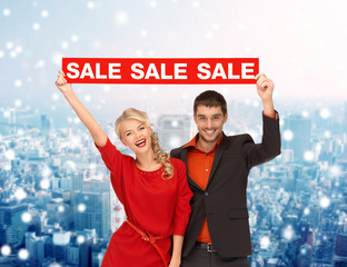 smiling couple with red sale sign