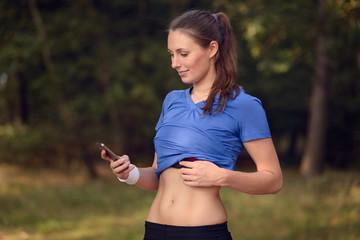 Junge athletische Frau schaut auf ihr Smartphone