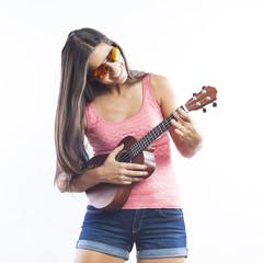 young beautiful brunette woman playing ukulele and having fun