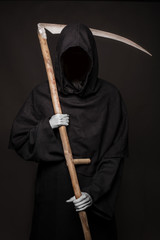 Angel of death with a scythe in his hands on black background