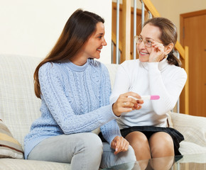 Happy woman and her daughter with pregnancy test