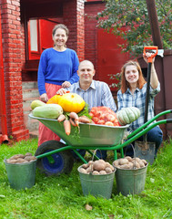 Man and two women with  harvested vegetables