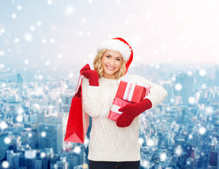 smiling young woman in santa helper hat with gifts