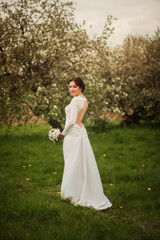 Pretty brunette bride standing with a bouquet in the garden