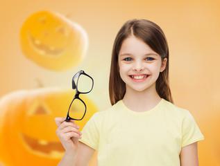 smiling girl in glasses over pumpkins background