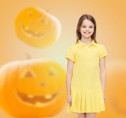 smiling girl in dress over pumpkins background