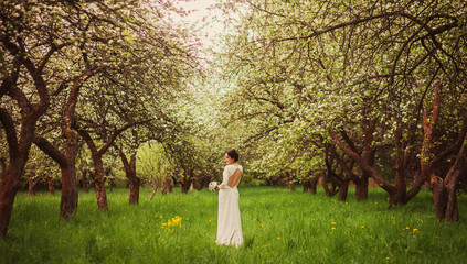 Beautiful bride stands alone in the garden