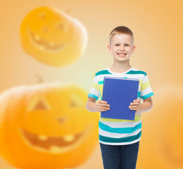smiling little student boy with blue book