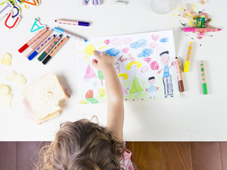 Little girl point at a sun in drawing of multi-racial Family