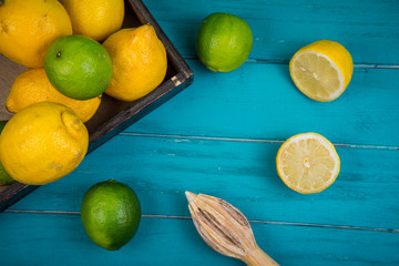 Organic lemons and limes with squeezer on table