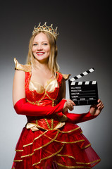 Queen in red dress with movie clapboard