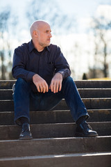 Thoughtful man sitting on a flight of steps