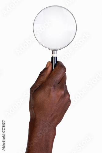 Man's hand holding magnifying glass - 70738217