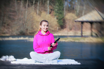 Sport teenage girl using tablet touchpad on pier