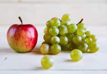 apples with grapes on wooden background