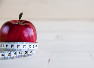 Diet concept with red apple and measuring tape