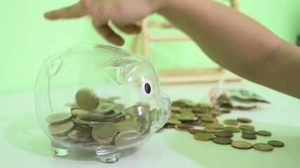 child puts coins in the piggy bank