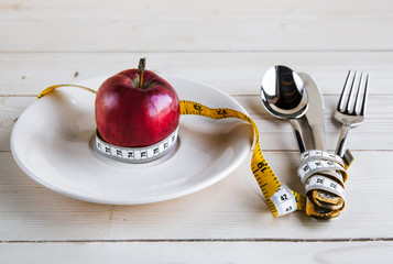 plate with apple measure tape, knife and fork.