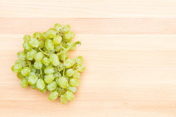 White grapes on a wooden cutting board