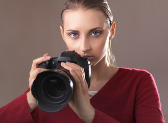 Beautiful young woman with camera. isolated on grey