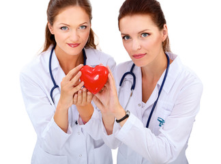Two woman doctor holding a red heart, isolated on white