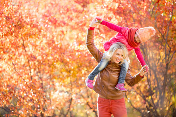 Happy mother and kid having fun together outdoor in autumn or fa