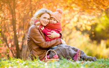 Mother and kid sitting and hugging together in autumn park.
