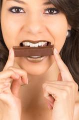 beautiful young brunette girl eating chocolate