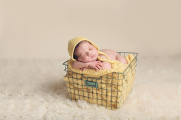 Newborn wearing a yellow hat in a basket