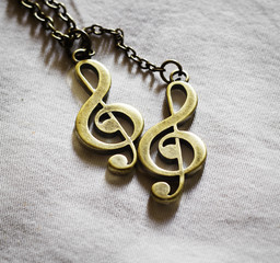 Metal music clef on fabric background